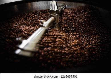 roasted  spinning cooler professional machines and fresh brown coffee beans movement close up dark photo at factory chiang rai Thailand