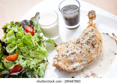 Roasted steak chicken on the table with sauce and salad