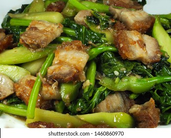 Roasted streaky pork with Chinese kale(Broccoli) on the white plate. Fried with oyster sauce, fish sauce and sugar. Favorite and famous menu in Asia. Fast food and street food concept.