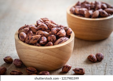Roasted striped peanuts in wooden bowl