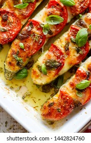Roasted, stuffed zucchini with the addition of tomatoes, mozzarella cheese, fresh basil and olive oil (caprese salad) in a ceramic baking dish, close-up, top view. Nutritious and tasty vegetarian dish