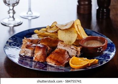 roasted sucking pig with potato chips and souce/Traditional Portuguese cuisine