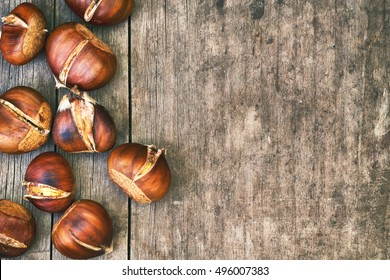 Roasted sweet chestnuts on grey rustic wooden table. Top view with plenty of copy space