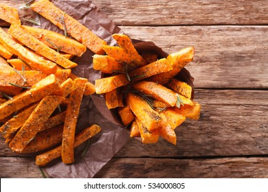 roasted sweet potatoes with herbs in a paper cone closeup on the table. Horizontal view from above
