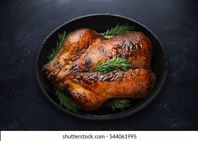 Roasted Thanksgiving Day Turkey with rosemary in black pot on table.