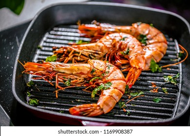 Roasted tiger prawns in iron grilling pan with  lemon, black background, top view