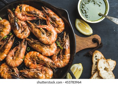 Roasted tiger prawns in iron grilling pan with fresh leek, lemon slices, bread and pesto sauce over black background, top view, horizontal composition