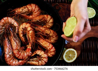 Roasted tiger prawns on a hot cast iron  fried in butter with lime and herbs in the restaurant. Process of cooking. Shrimp on the grill.  Exquisite dish of seafood. Food background. Selective focus.