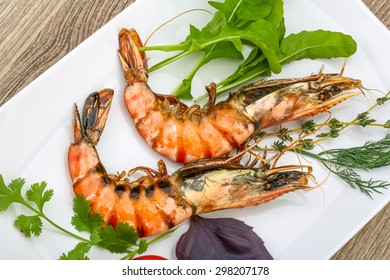 Roasted tiger shrimps with thyme and basil leaves