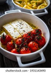 geröstete Tomaten mit Feta-Käse und Penne in Keramikpfanne auf Holztisch