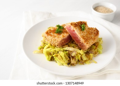 roasted tuna steak in sesame seeds with savoy cabbage vegetable, on a plate on a white table, copy space, selected focus, narrow depth of field