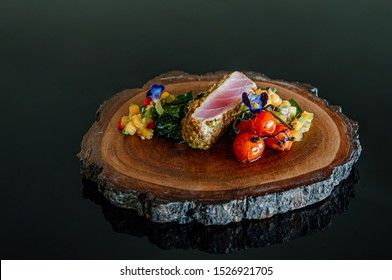 Roasted Tuna Steaks Crusted with Herbs and grilled vegetable and mango salsa on wood plate isolated on black background