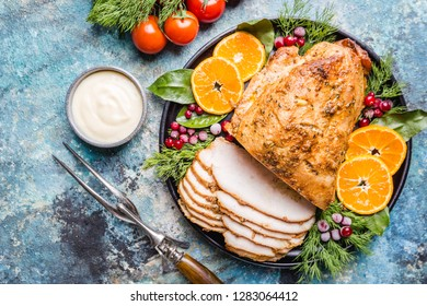Roasted turkey breast for festive dinner on dark stone background, top view with copy space