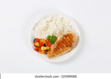 roasted turkey breast with rice and grilled vegetables on white plate