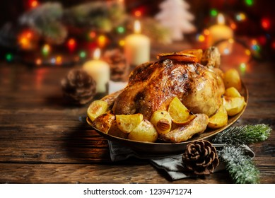 Roasted turkey or chicken with orange slices and potatos in plate for Christmas dinner served with festive decoration on rustic background.