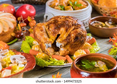Roasted turkey garnished with corn and many dishes on a rustic wooden table.
