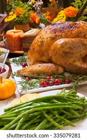 Roasted turkey garnished with cranberries on a rustic style table decoraded with pumpkins, gourds, asparagus, brussel sprouts, baked vegetables, pie, flowers, and candles.