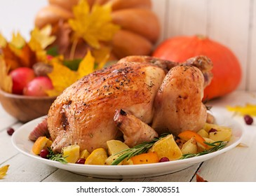 Roasted turkey garnished with cranberries on a rustic style table decorated with pumpkins, orange, apples and autumn leaf.