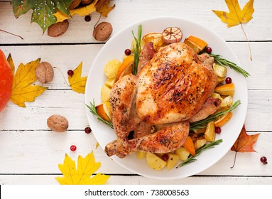 Roasted turkey garnished with cranberries on a rustic style table decorated with pumpkins, orange, apples and autumn leaf. Flat lay. Top view