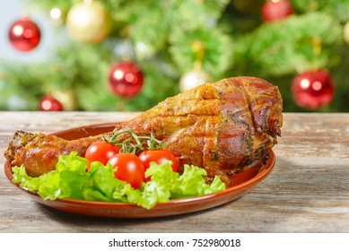 Roasted turkey leg with vegetables over christmas tree background.