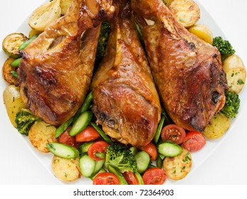Roasted turkey legs with vegetables.