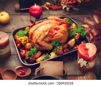 Roasted Turkey. Thanksgiving Dinner. Thanksgiving table served with turkey, decorated with bright autumn leaves. Table setting with greeting card