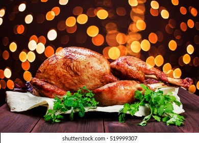 Roasted Turkey. Thanksgiving table served with turkey, decorated with greens and basil on dark wooden background. Homemade roasted chicken. Christmas holiday dinner