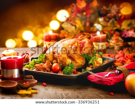 Roasted Turkey. Thanksgiving table served with turkey, decorated with bright autumn leaves and candles. Roasted chicken, table setting. Christmas dinner