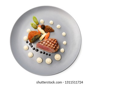 roasted veal, morels, vegetables and a fried potato stuffed with onion seeds on a blue plate isolated on a white background, high angle view from above, selected focus, narrow depth of field