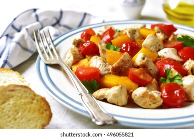 Roasted vegetables with chicken on a vintage plate on a concrete or stone background.