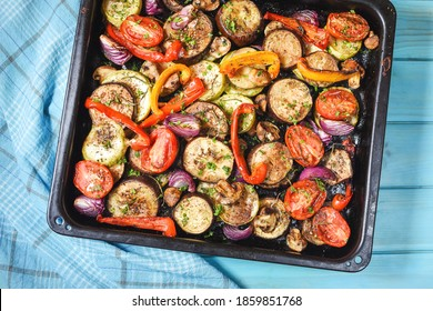 Roasted vegetables mix on baking tray on blue wooden background. Top view