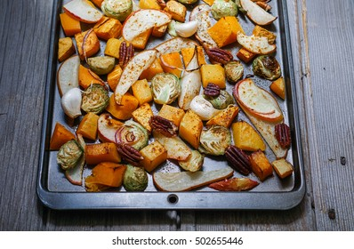 Roasted vegetables on a baking sheet: sweet potato, butternut squash, brussels sprouts, apple, pecans and pear. Toning. Healthy eating concept. Close-up, selective focus.