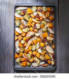 Roasted vegetables on a baking sheet: sweet potato, butternut squash, brussels sprouts, apple, pecans and pear. Toning. Healthy eating concept. Top view.
