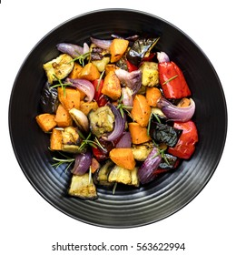 Roasted vegetables on black platter.  Top view, isolated on white.