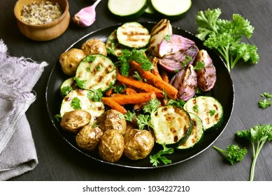 Roasted vegetables on black stone table. Close up view