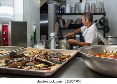 Roasted vegetables on trays with a chef preparing for diner service in the background
