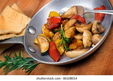Roasted vegetables in a pan with rosemary
