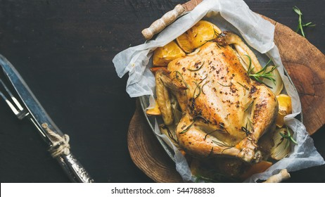 Roasted whole chicken stuffed with oranges, bulgur and rosemary on wooden board and cutlery over dark wooden background. Top view, copy space, Slow food concept