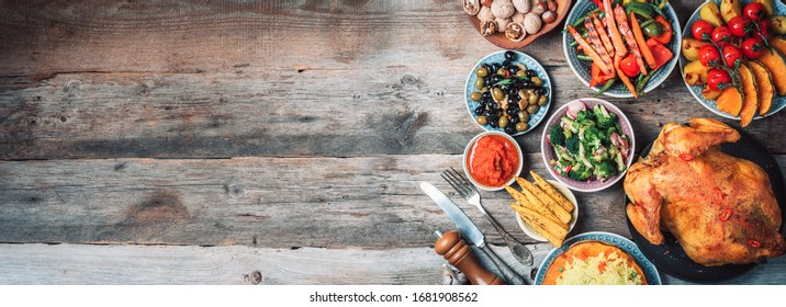 Roasted whole chicken or turkey, pumpkins, corn and harvest vegetables with kitchen knife and cutlery served around aged wooden cutting board on dark rustic background, frame. Thanksgiving Day food