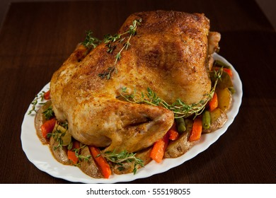 Roasted whole chicken with vegetables and thyme on a wooden background