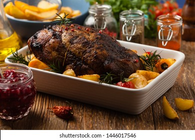 Roasted whole shoulder, with potatoes, peppers and tomatoes. Marinated in white wine. Front view. Natural wooden background.