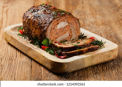 Roasted whole, stuffed with minced pork neck. Front view. Natural wooden background.