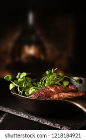 Roasted wild duck breasts in wrought iron skillet with fresh watercress salad shot against a rustic background with accommodation for copy space.