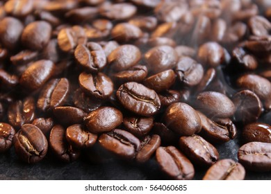 Roasting coffee beans in a pan releasing fresh aromatic smoke & steam. A dark and inviting photograph.