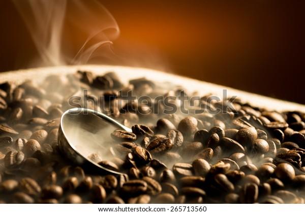 Roasting coffee beans with smoke on dark background