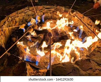 Roasting marshmallows over an open fire pit.