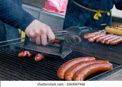 Roasting sausages on charcoal in the outdoor. The man's hand presses the sausages to the grate