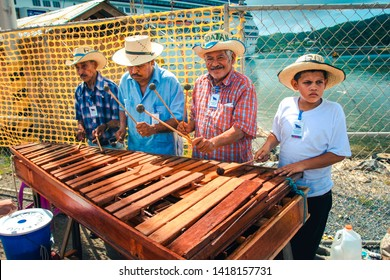 Roatan / Honduras - November 22.2007 : Group of local street musicians playing folk music on the wooden cymbals instrument. Dressed in the colorful shirts and straw hats on the head. Sunny day.