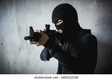 Robber assassin crime with hood holding M16 the gun points already shoot