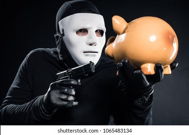 Robber in balaclava and mask aiming at piggy bank